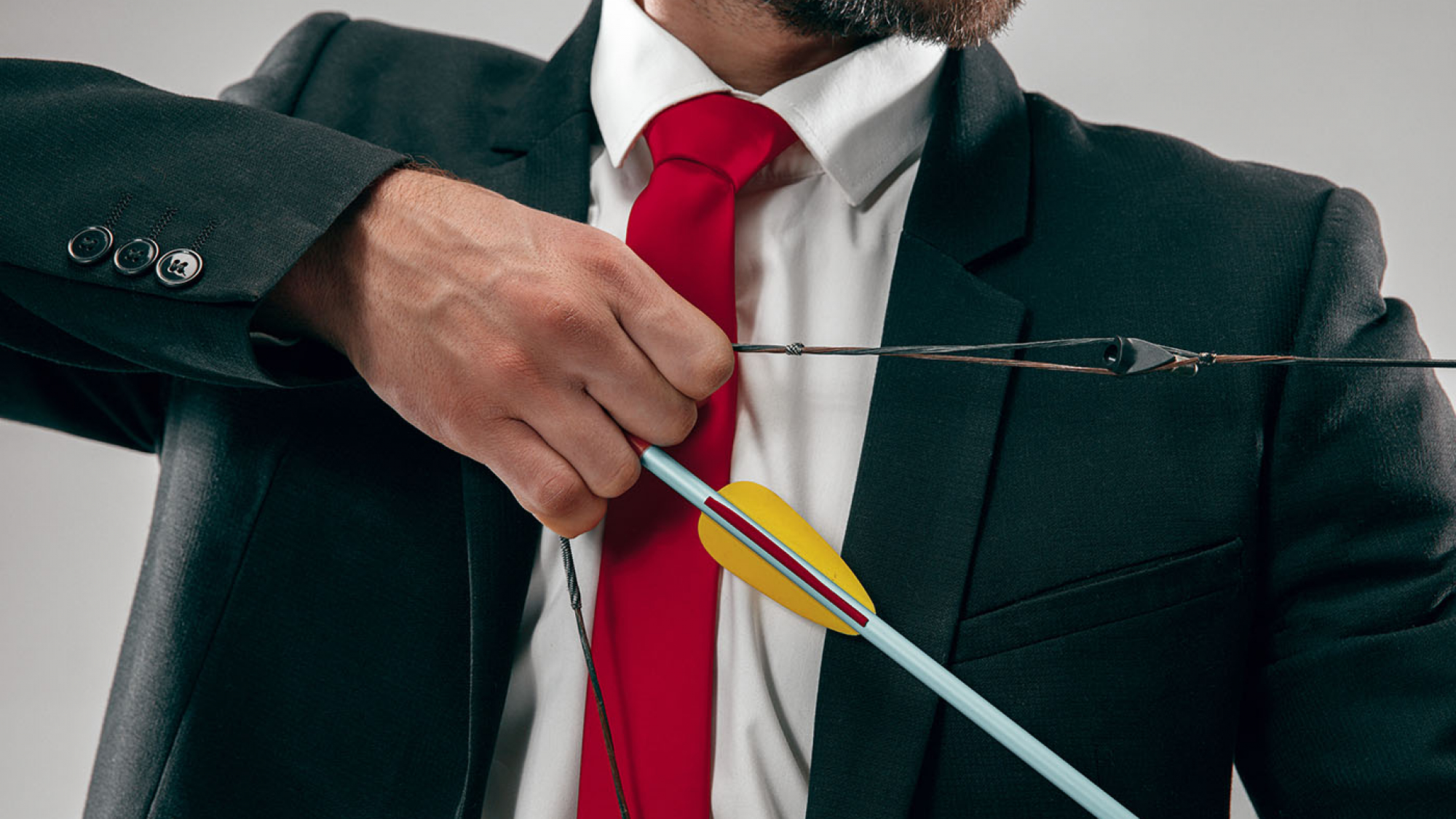 Businessman aiming at target with bow and arrow isolated on gray studio background. The business, goal, challenge, competition, achievement, purpose, victory, win, clarity, winner and success concept